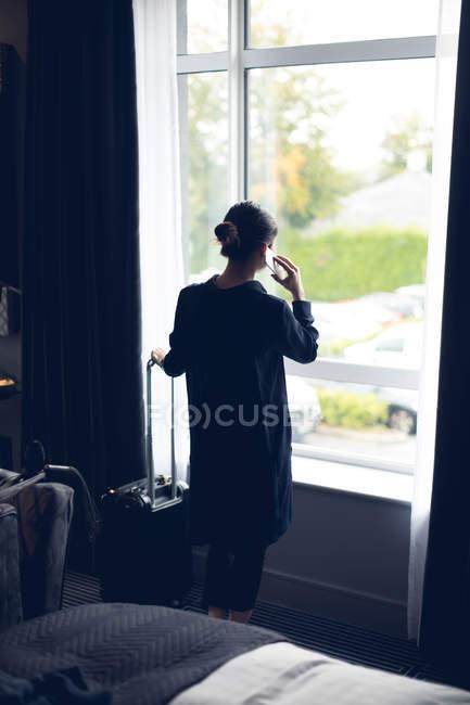 Задній вид жінка говорити на мобільний телефон у готельному номері — стокове фото