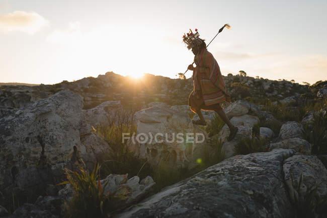 Maasai Mann in traditioneller Kleidung zu Fuß auf Felsen — Stockfoto