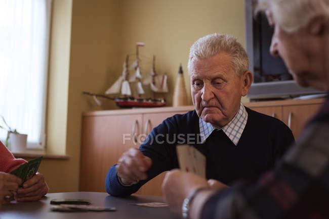 Seniorenfreunde spielen Karten im Pflegezimmer — Stockfoto