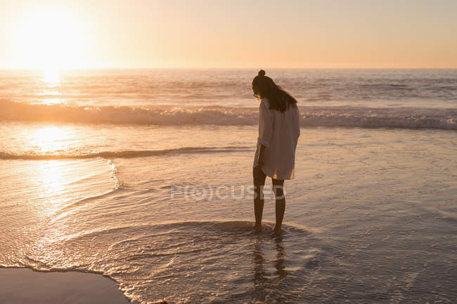 Woman standing in sea water on beach at dusk. — Stock Photo