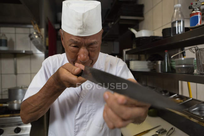 Senior chef tenant le couteau de cuisine au restaurant — Photo de stock