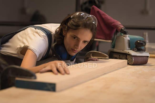 Junge Handwerkerin begutachtet Vorstand in Werkstatt. — Stockfoto