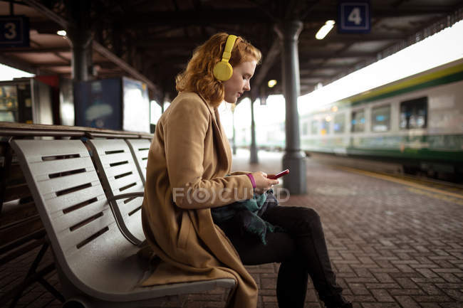 Young woman listing music while using her mobile phone at railway platform — Stock Photo