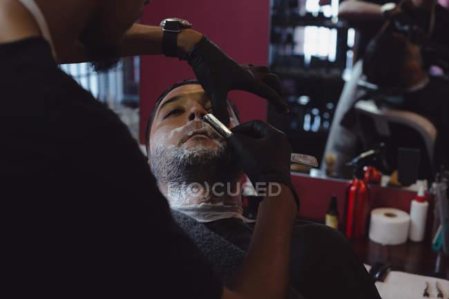 Человек, получать его борода, побрился с бритвой в парикмахерской — стоковое фото