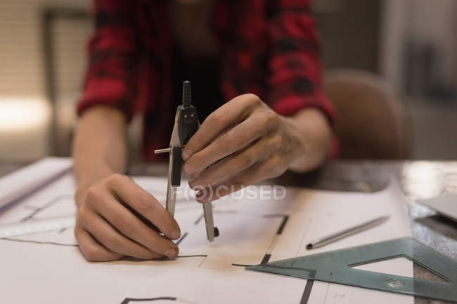 Mid section of female engineer using compass in workshop. — Stock Photo