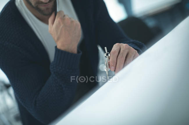 Executive working on blueprint in modern office — Stock Photo