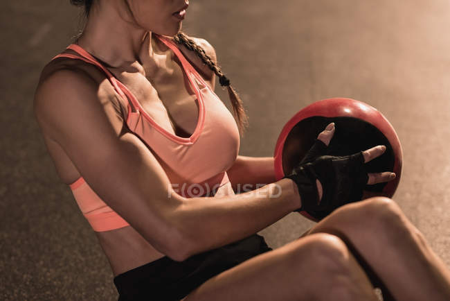 Mid section of fit woman exercising with equipment in the studio — Stock Photo
