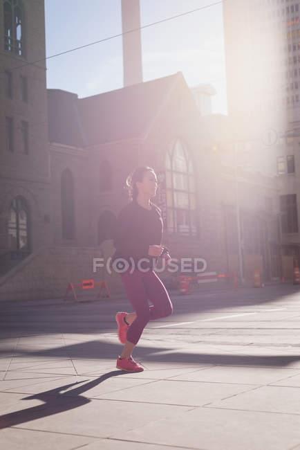 Подтянутая женщина согревается на улице в солнечный день — стоковое фото
