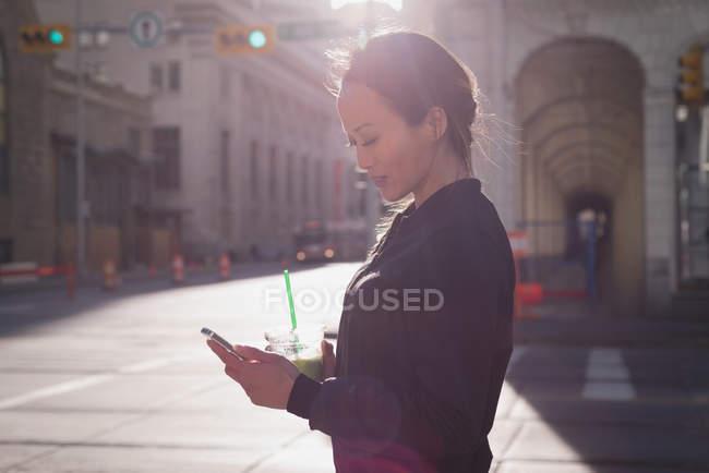 Женщина с помощью мобильного телефона во время с напитком на улице — стоковое фото