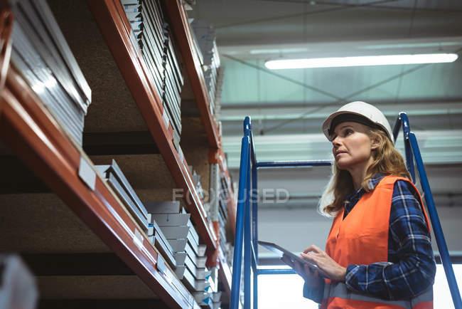 Arbeiterin hält Rekord auf digitalem Tablet im Werkslager — Stockfoto