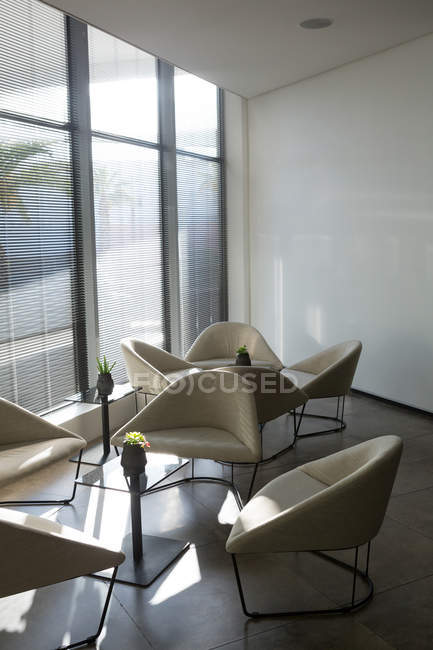 Empty table and chairs in waiting area of office on a sunny day — Stock Photo