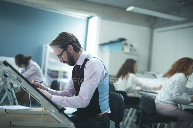 Male executive working over drafting table in modern office — Stock Photo