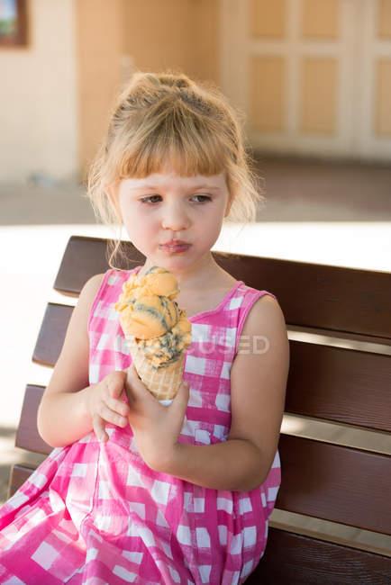Милая девушка ест мороженое в солнечный день — стоковое фото