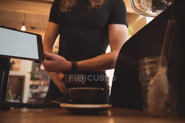 Client d'effectuer le paiement avec smartwatch au comptoir de la cafétéria — Photo de stock