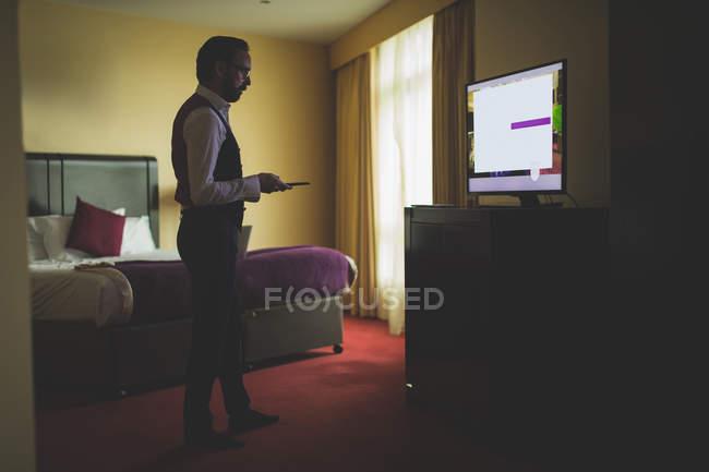Empresário assistindo tv no quarto do hotel — Fotografia de Stock