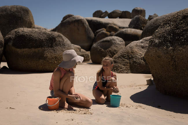 Mother and daughter playing in sand at beach — Stock Photo