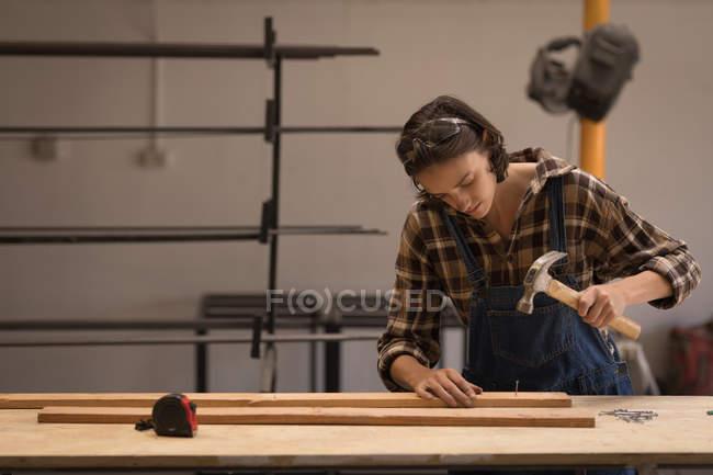 Молода жінка ремісник роботи з молотом в майстерні. — стокове фото