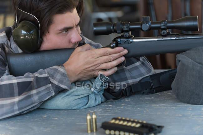 Vista lateral do homem apontando o rifle sniper no alvo no tiro ao alvo — Fotografia de Stock