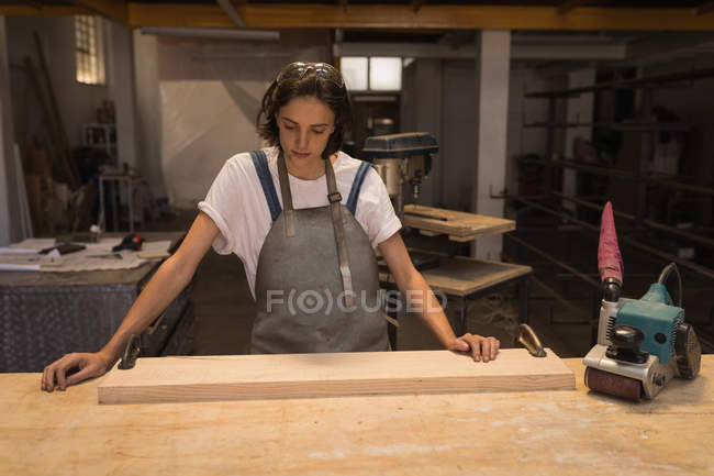 Young female artisan working with wood in workshop. — Stock Photo