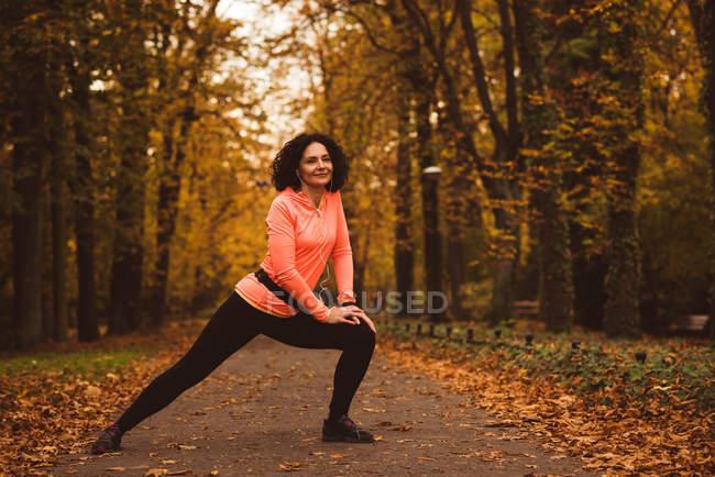 Lächelnde Frau bei Stretching-Übung im Wald — Stockfoto