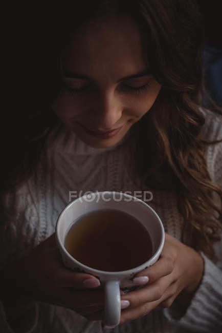 Gros plan de belle femme sentant l'arôme du thé — Photo de stock