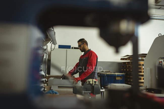 Trabalhador masculino reparando uma máquina com ferramenta na fábrica — Fotografia de Stock