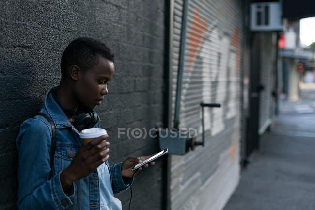 Женщина пьет кофе, пользуясь мобильным телефоном. — стоковое фото