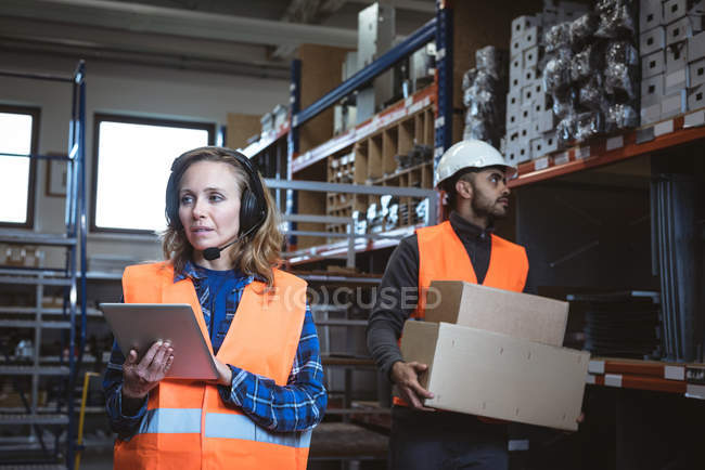 Female worker maintaining record on digital tablet at factory warehouse — Stock Photo