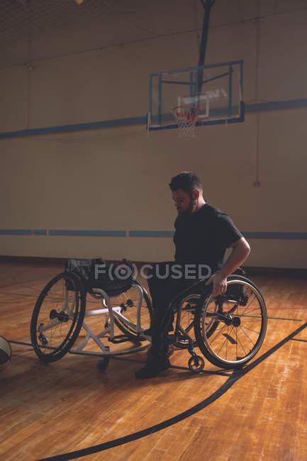 Інвалідів молода людина в інвалідному візку на баскетбольний майданчик — стокове фото