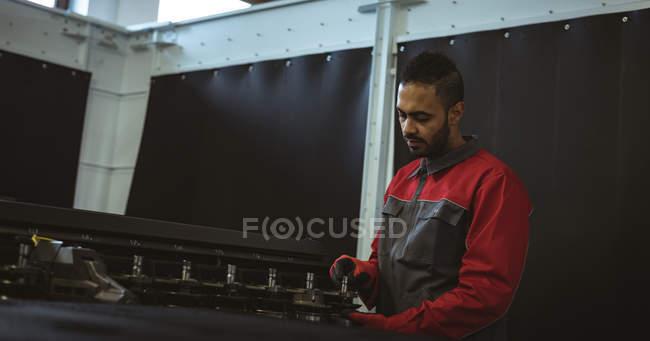 Чоловічий працівник перевірки машини частина заводі — стокове фото