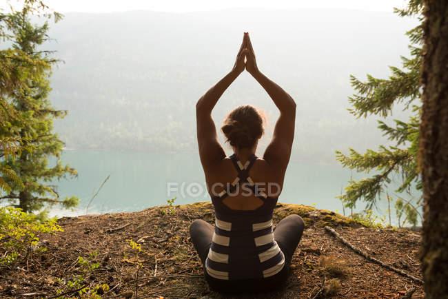 Femme apte à effectuer des exercices d'étirement dans une forêt luxuriante au moment de l'aube — Photo de stock