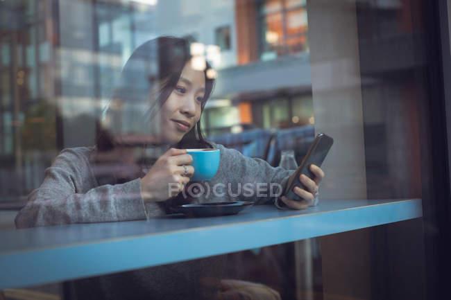Belle femme utilisant un téléphone portable tout en prenant un café à la cafétéria — Photo de stock