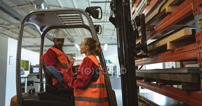 Mitarbeiter interagieren in Fabriklager miteinander — Stockfoto