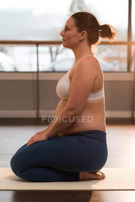 Вид сбоку беременной женщины, занимающейся йогой — стоковое фото
