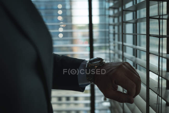 Cropped image of Businessman checking time on wrist watch at hotel — Stock Photo