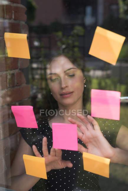 Жіночий виконавчий дивлячись наліпок в офісі — стокове фото