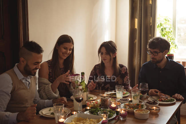 Friends interacting while having meal at table — Stock Photo
