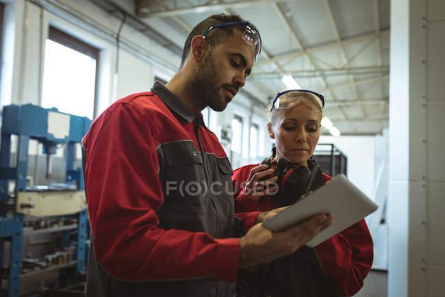 Dos trabajadores discutiendo sobre tableta digital en fábrica - foto de stock