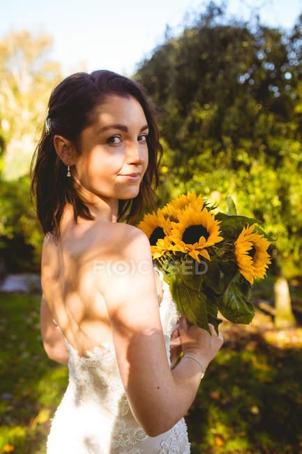 Портрет красивая невеста, держа подсолнечника букет в саду — стоковое фото