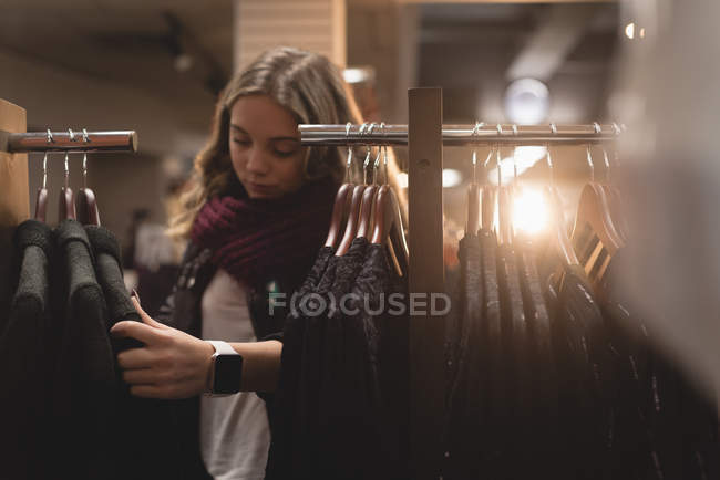 Beautiful girl selecting dress from rack in shopping mall — Stock Photo