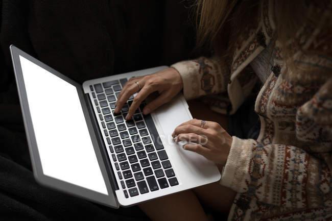 Partie médiane de la femme utilisant un ordinateur portable à l'intérieur . — Photo de stock