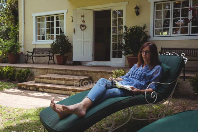 Livre de lecture femme sur fauteuil dans le jardin — Photo de stock