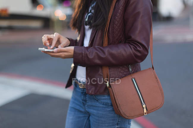 Mid section of woman using mobile phone in city street — Stock Photo