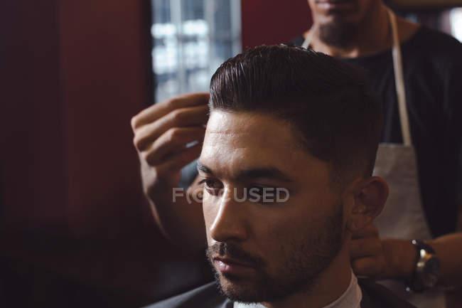 Homem recebendo seu cabelo aparado com tesoura na barbearia — Fotografia de Stock