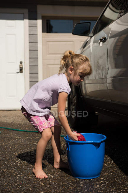 Girl washing a car at outside garage on a sunny day — Stock Photo