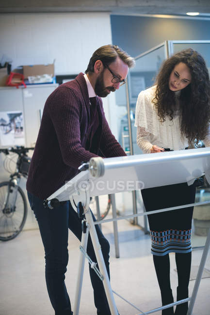 Executives working on drafting table in modern office — Stock Photo