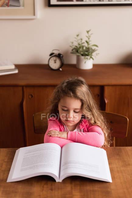 Studieux fille lisant un livre à la maison — Photo de stock