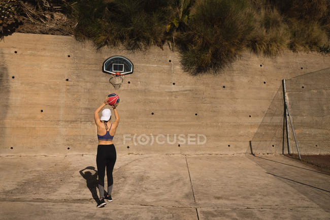 Вид сзади женщины, играющей в баскетбол на баскетбольной площадке — стоковое фото