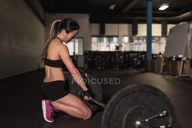Фигуристка корректирует штангу в фитнес-студии — стоковое фото
