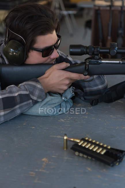 Крупный план человека, целящего снайперскую винтовку в цель на стрельбище — стоковое фото